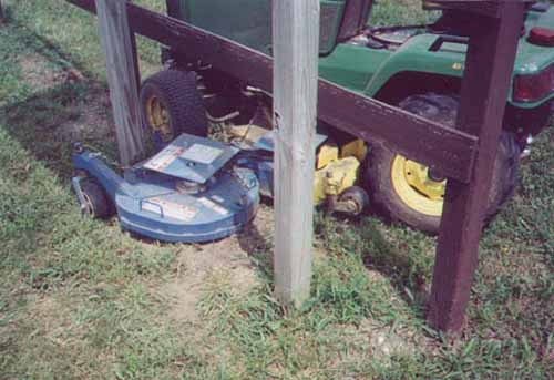 JD tractor under fence and sign.jpg